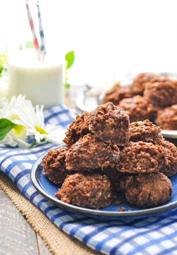 amish no bake cookies stacked on a blue plate with a blue napkin underneath