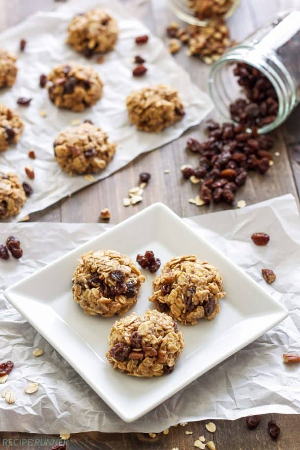no bake oatmeal raisin cookies on a white plate with raisins spilling out from jar