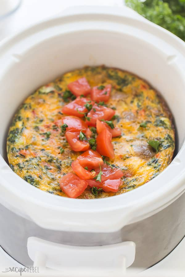 breakfast casserole in a white crockpot with fresh tomatoes on top