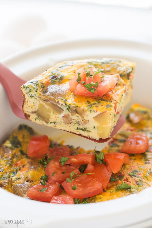 triangle slice of breakfast casserole being pulled out of crockpot on a red spatula