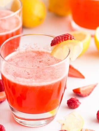 pink lemonade recipe in a glass with strawberry and lemon