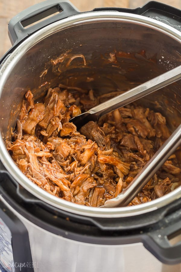 pulled pork with cranberry bbq sauce in the pressure cooker with metal tongs stuck in