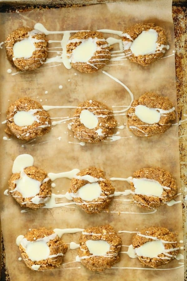 no bake lemon thumbprint cookies on piece of parchment paper with glaze drizzle over top
