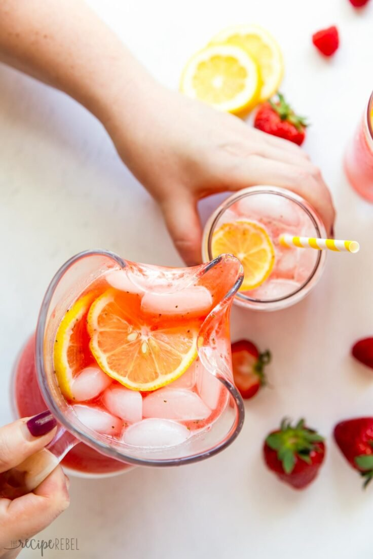 pouring pink lemonade from pitcher into glass