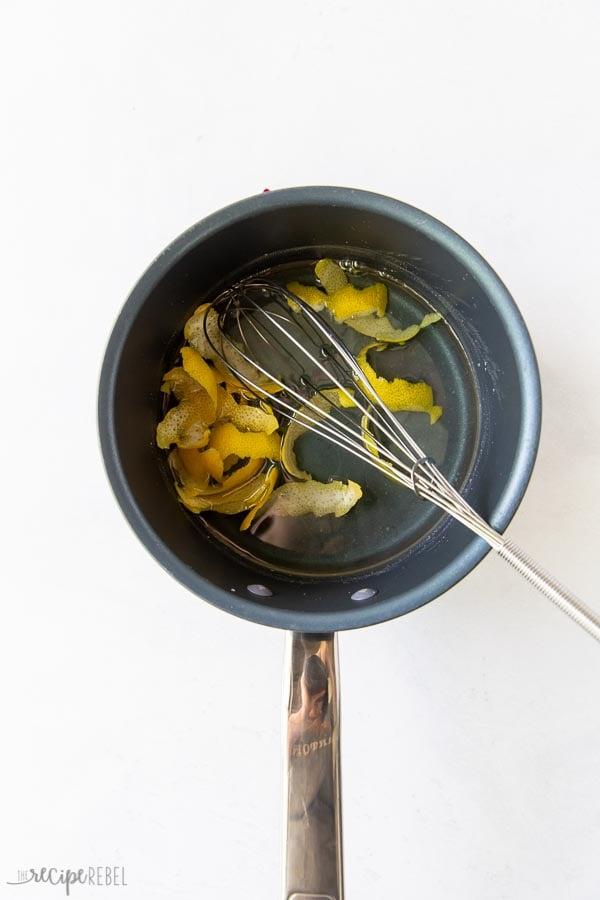 simple syrup with lemon peel strips in pan