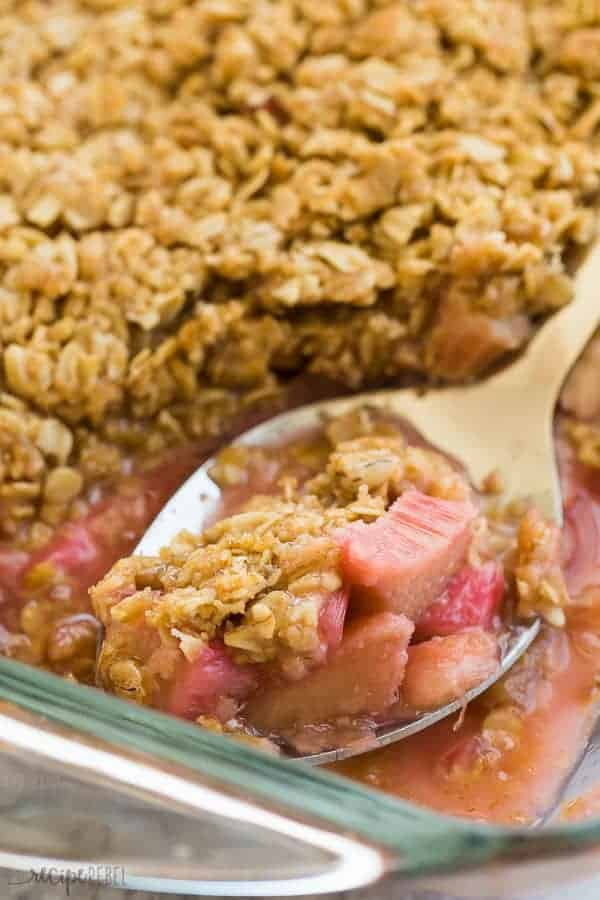 close up image of rhubarb crisp on a metal serving spoon in a glass pan