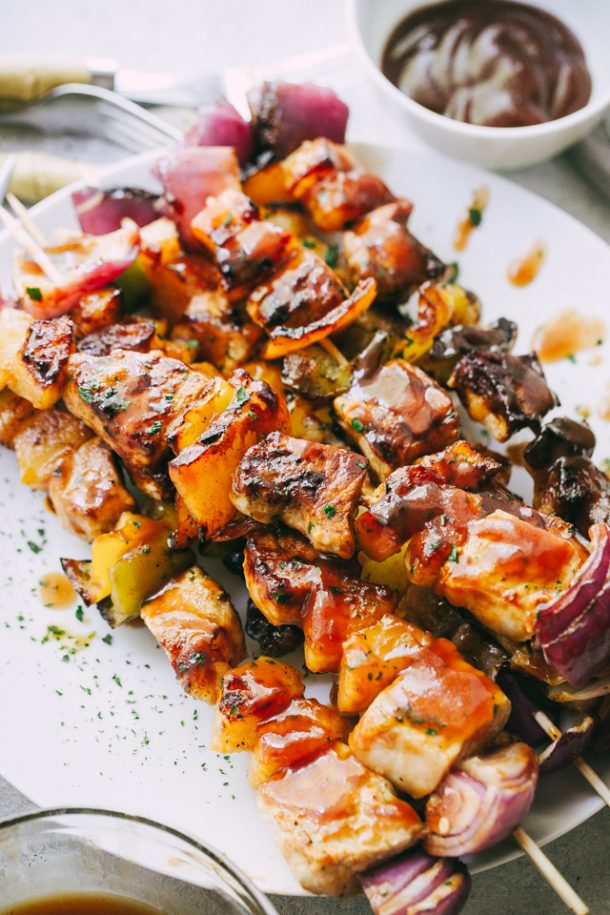 barbecue pineapple and pork skewers on white plate with barbecue sauce in the background