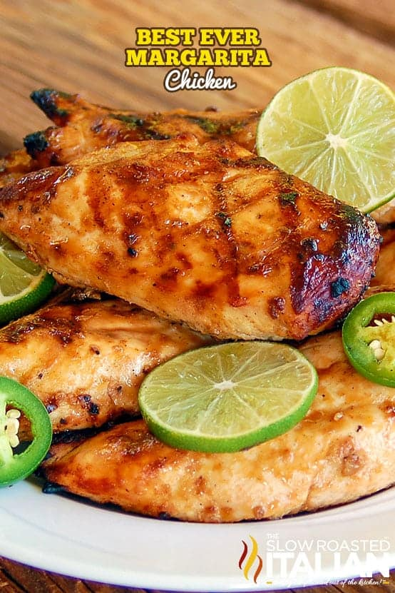 grilled margarita chicken stacked on white plate with fresh lime slices