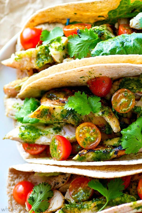 greek marinated grilled chicken tacos close up on tortillas with fresh tomatoes and cilantro