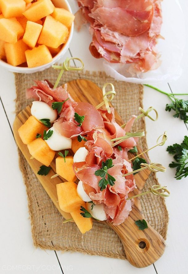melon prosciutto and mozzarella skewers on gold skewers on top of wooden cutting board with melon chunks on the side