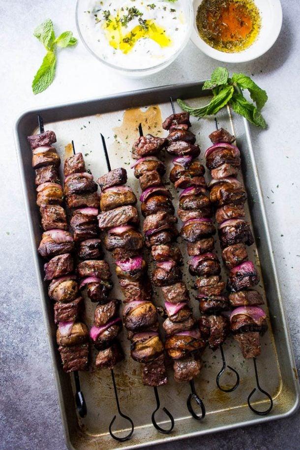 steak mushroom kabobs with mint yogurt dip on a sheet pan with fresh mint leaves