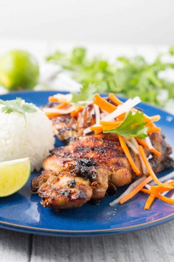 vietnamese lemongrass grilled chicken thighs on blue plate with white rice topped with carrot matchsticks