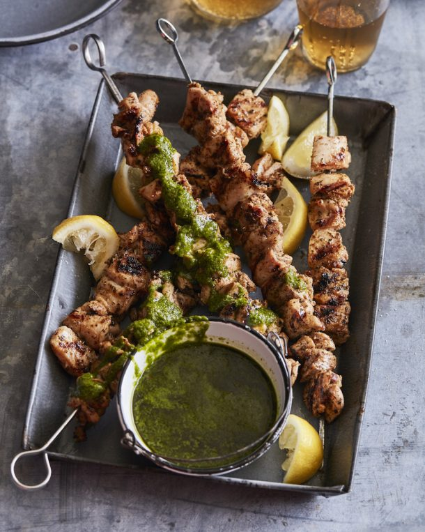 chicken shish kabobs on metal skewers on a grey metal plate with lemon wedges on the side