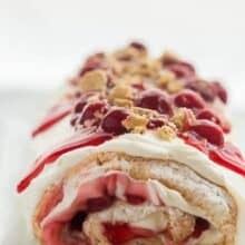 cherry cheesecake roll whole on a white plate