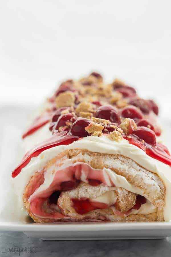cherry cheesecake roll whole on a white plate with cherry pie filling and crushed graham crackers on top