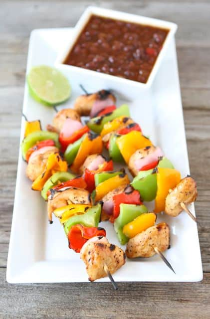 grilled chicken fajita kabobs on white plate with lime half and salsa on the plate