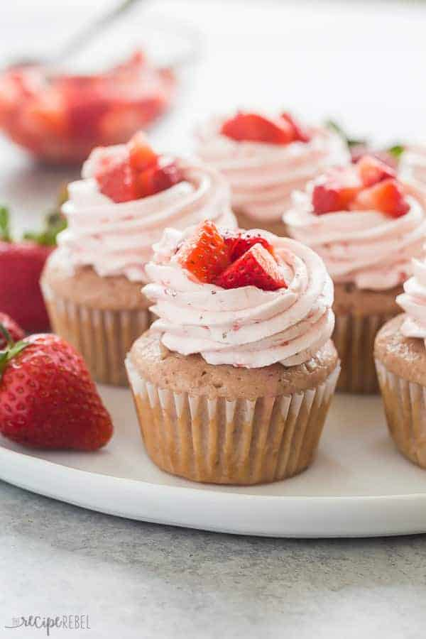 strawberry cupcakes with strawberry frosting on a white plate