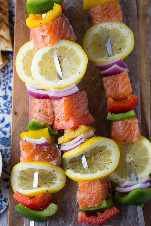 souvlaki salmon kabobs close up with fresh lemon slices uncooked
