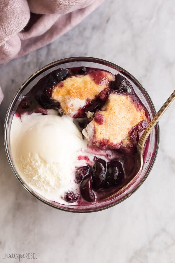 close up image of bowl of cherry cobbler with vanilla ice cream with spoon