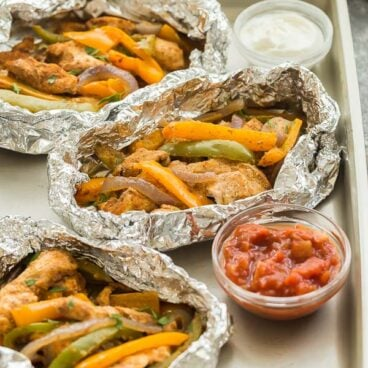 This Chicken Fajita Foil Packets is a family favorite! Easy to customize, loaded with chicken, peppers, red onions and a homemade fajita seasoning, and perfect for making ahead for an easy camping meal! #foilpack #foilpacket #chicken #grill #grilling #dinner #recipe