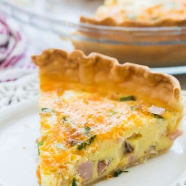 This Easy Ham Quiche recipe started with a refrigerated pie crust or you can make your own! It's filled with ham, cheese, green onions and perfectly seasoned. The perfect breakfast, dinner, or holiday brunch item! #eggs #breakfast #brunch #ham #dinner #recipe