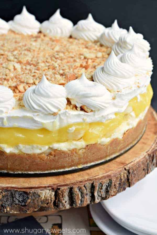 no bake banana cream cheesecake whole with whipped cream swirls and crushed wafers on top