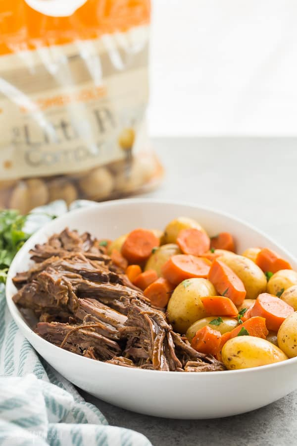 instant pot pot roast on white platter with bag of little potatoes in the background