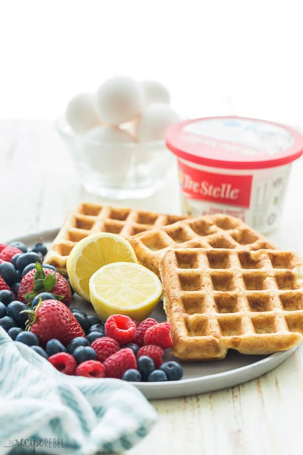 lemon ricotta waffles on a plate with lemon halves fresh berries and a tub of ricotta cheese in the background