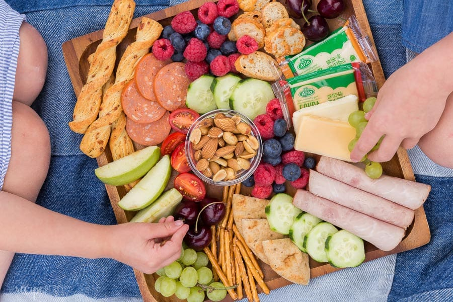 kids snack board on wooden board with two children reaching for snacks