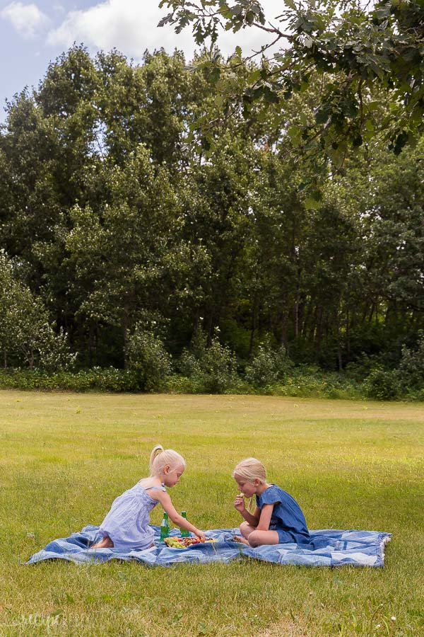 two young girls having a picnic on a denim picnic blanket with trees in the background