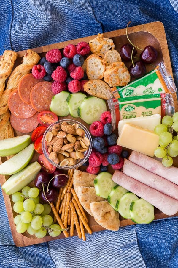 kid friendly summer cheese board overhead on wooden board on denim blanket with fresh fruit and vegetables crackers and cheese