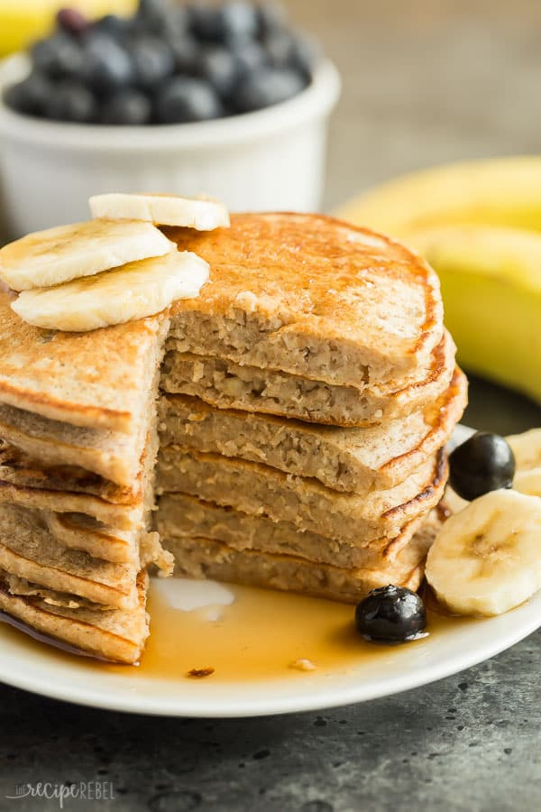 banana oatmeal pancakes stack on a plate with one wedge cut out of stack and syrup on plate