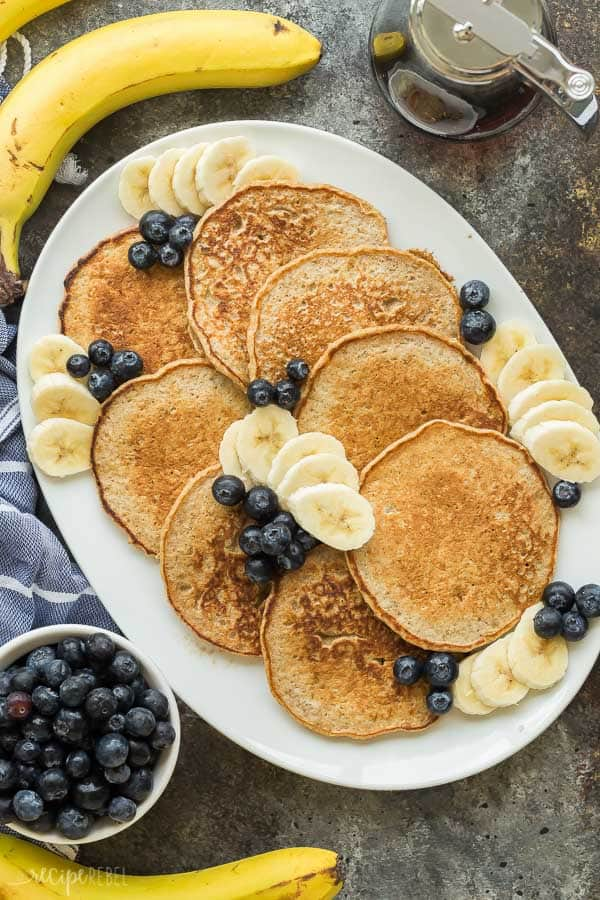 banana oatmeal pancakes on a platter with fresh blueberries and banana slices all around on a dark grey background
