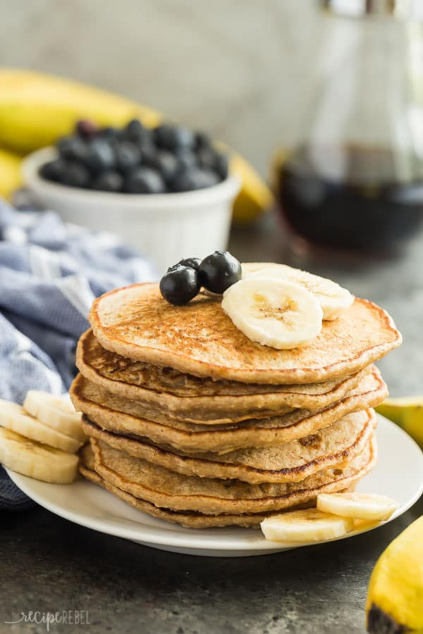 banana pancakes stack on white plate with fresh blueberries and banana slices on top