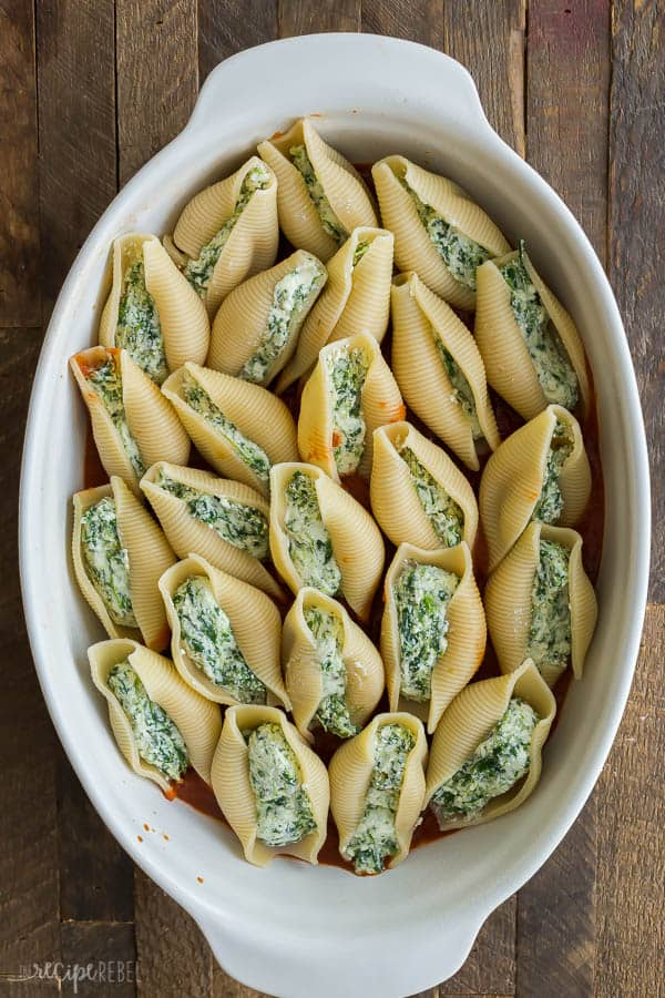 ricotta stuffed shells unbaked filled with ricotta and spinach mixture on wooden background