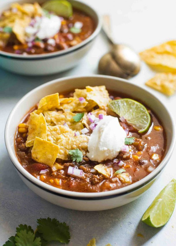 ground beef slow cooker taco soup two bowls topped with tortilla chips sour cream and lime slice