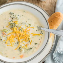 instant pot broccoli cheese soup with shredded cheese on top