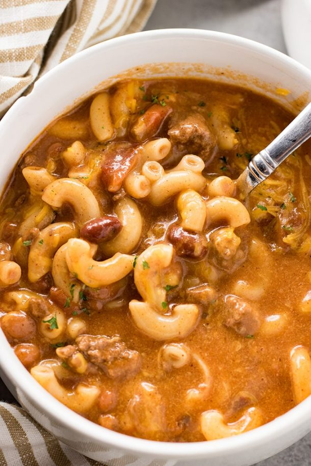 ground beef crock pot chili macaroni soup very close up image with metal spoon stuck into soup
