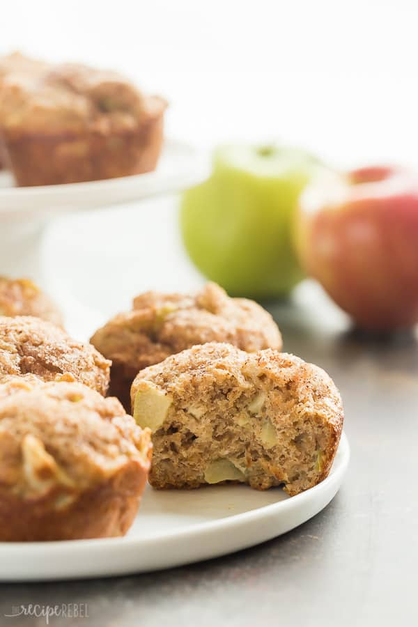 cinnamon apple muffins on a plate with a bite taken out of one muffin
