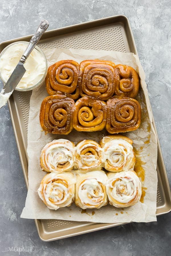 cinnamon buns on rimmed sheet pan on piece of parchment paper with half frosted and half gooey caramel