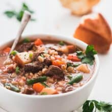 bowl of instant pot beef barley soup with a spoon in