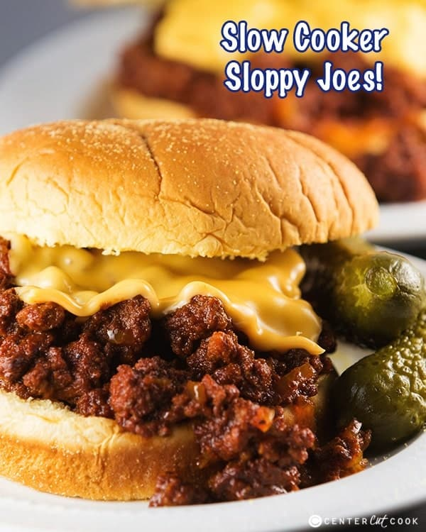 ground beef crock pot sloppy joes close up on white bun with melted cheese and pickles on the side