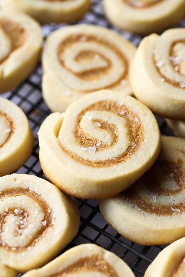caramel pinwheel christmas cookies up close on baking rack with flakes of salt