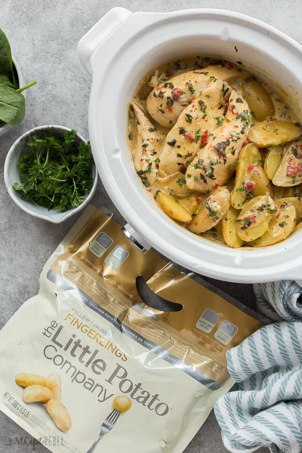 crockpot chicken and potatoes overhead with fresh parsley on the side and bag of little potatoes