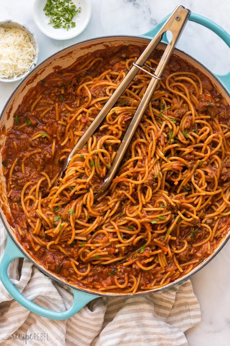 overhead image of one pot spaghetti with tongs stuck in