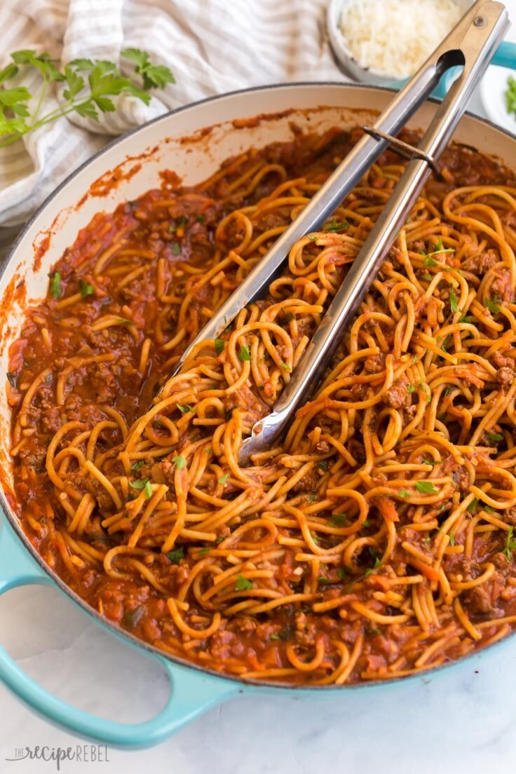 close up image of one pot spaghetti and meat sauce with tongs stuck in