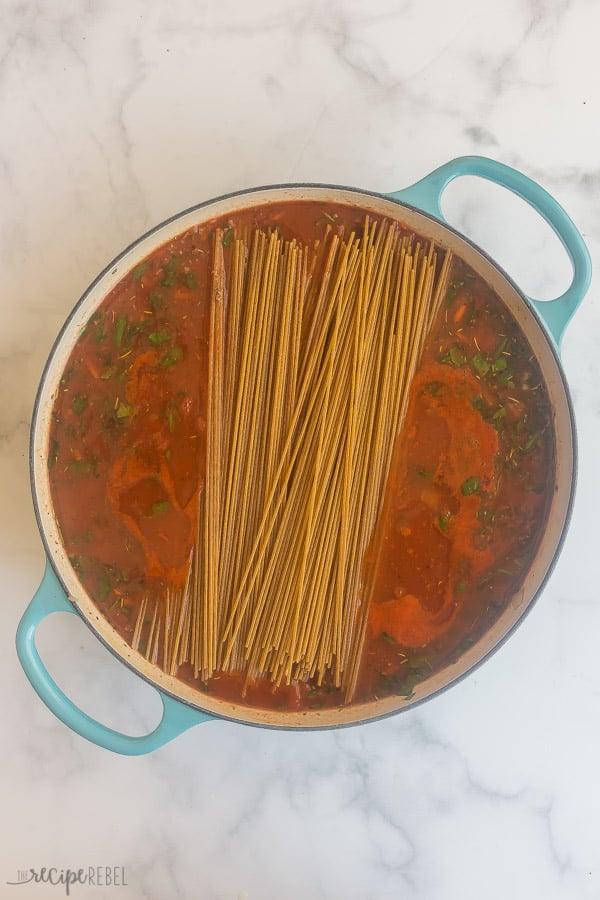 dry spaghetti added to spaghetti sauce in pan