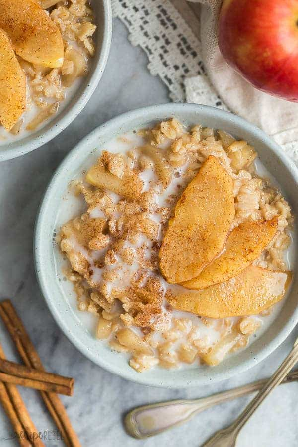 apple cinnamon oatmeal bowl overhead on grey marble background with spoons and cinnamon sticks on the side