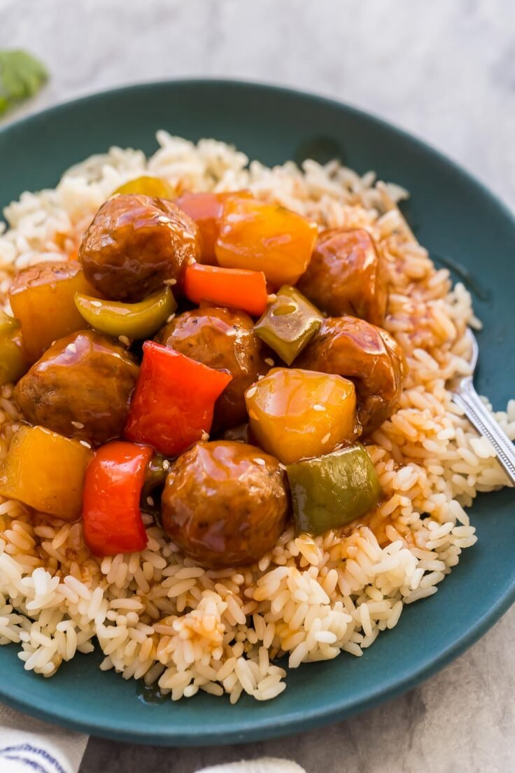 close up image of sweet and sour crockpot meatballs on a plate of rice