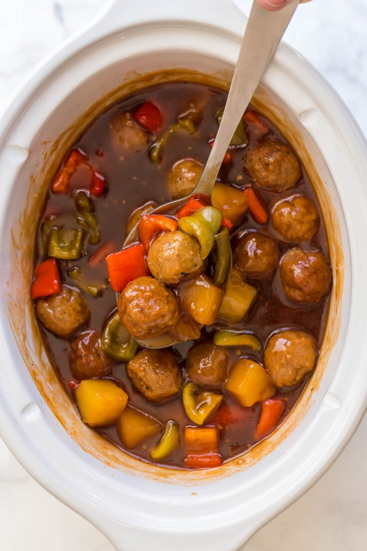 overhead image of crockpot meatballs with pineapples and peppers